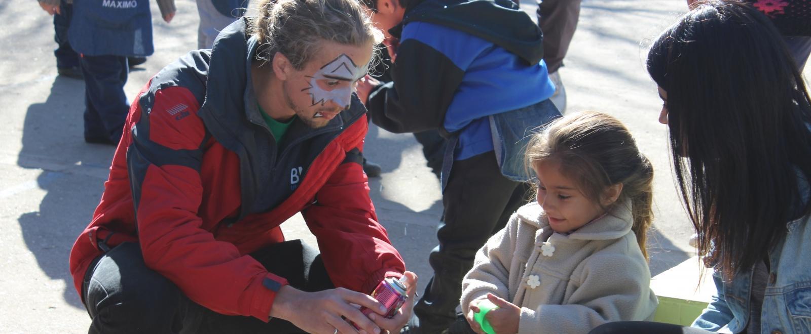 Projects Abroad vrijwilligers praten met een kind in Argentinie tijdens een community dag in een lokaal dagzorgcentrum.